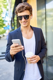 Stylish young man listening to music outdoors