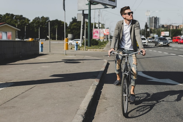 Stylish young man riding bicycle on street