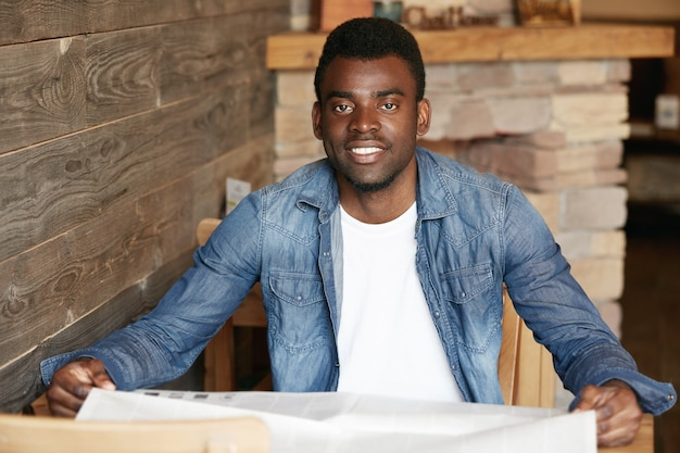 Elegante giovane uomo seduto nella caffetteria