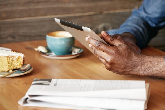 Стильный молодой человек сидит в кафе с планшетом