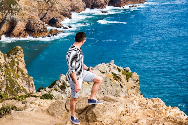岩の端に立っているスタイリッシュな若い男