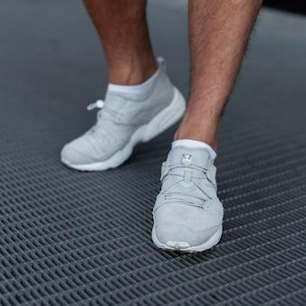 スタイリッシュな若い男がスポーツの白いスニーカーの金属の道に立っています。ファッショナブルなメンズシューズ。ストリートカジュアルスタイル。閉じる。
