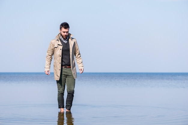 Stylish young man walking in the shallow sea water against blue sky