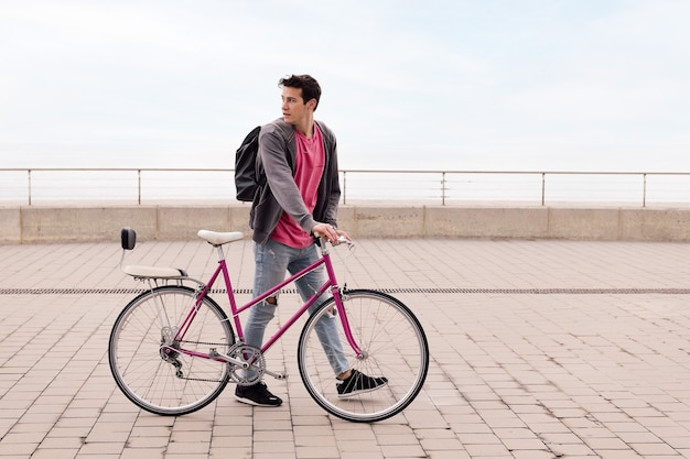 Stylish young man walking with a vintage bike concept of sustainable transportation