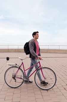 Stylish young man walking with a vintage bike