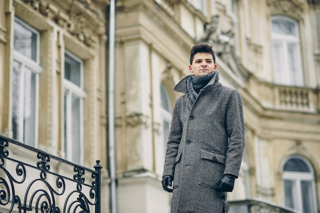 A stylish young man in a warm gray coat and leather gloves over old historic building.