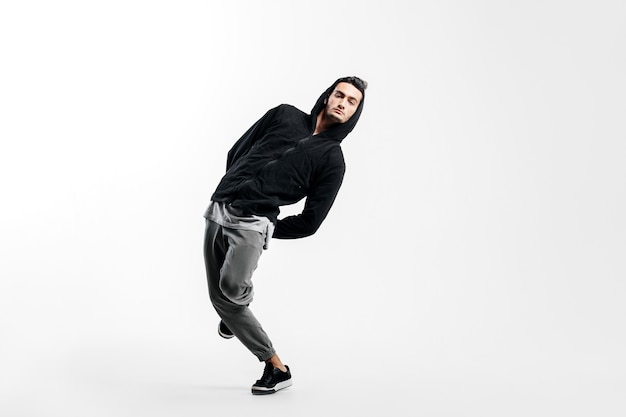 黒のスウェットシャツと灰色のズボンを身に着けているスタイリッシュな若い男は、白い背景の上でストリートダンスを踊っています