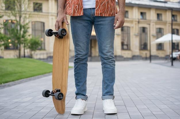 カジュアルな服を着て、スケートボードを保持している白い靴、公園に立っているスタイリッシュな若い男