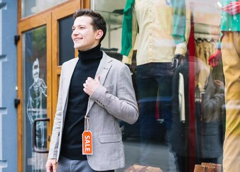 Stylish young man wearing jacket with sale tag standing outside the shop