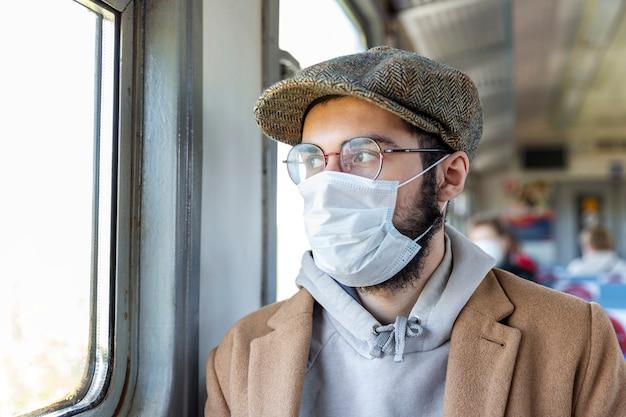 수염, 안경 및 기차에서 의료 마스크와 세련 된 젊은 남자는 창 밖으로 보인다. 코로나 바이러스 전염병 동안 자기 격리 체제와 사회적 거리. 확대. 예방 대책.