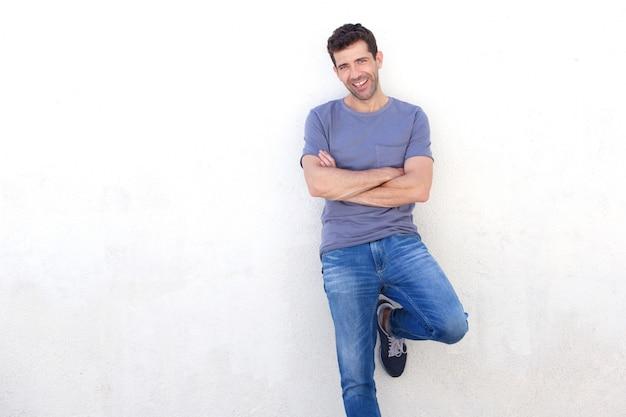 スタイリッシュな若い男は、白い壁に傾いて腕を越えて