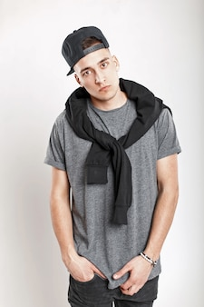 Stylish young man with a baseball cap in a gray t-shirt posing in the studio.