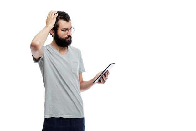 Stylish young man with a beard and glasses with a tablet in his hand. training, online communication, social networks and blogging.