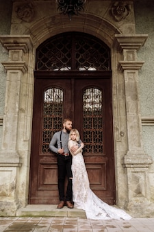 Stylish young man with beard and woman in luxury long dress on wedding day near the castle. romantic love in vintage atmosphere street.