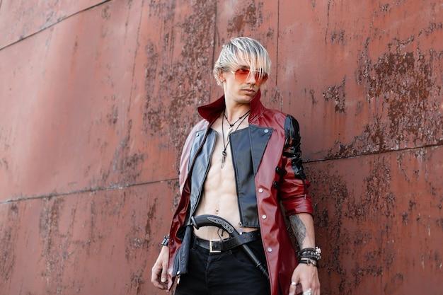 さびた壁の近くでポーズをとるヴィンテージの銃を持ったジーンズの革のジャケットのメガネのブロンドの髪を持つスタイリッシュな若い男。屋外の男。