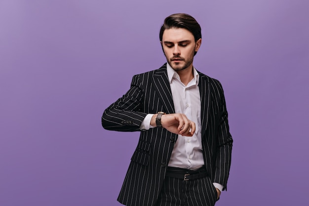 Stylish young man with brunette hair, white shirt and classic striped suit looking at watch on his hand isolated over violet wall