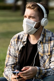 Stylish young man with face mask listening to music