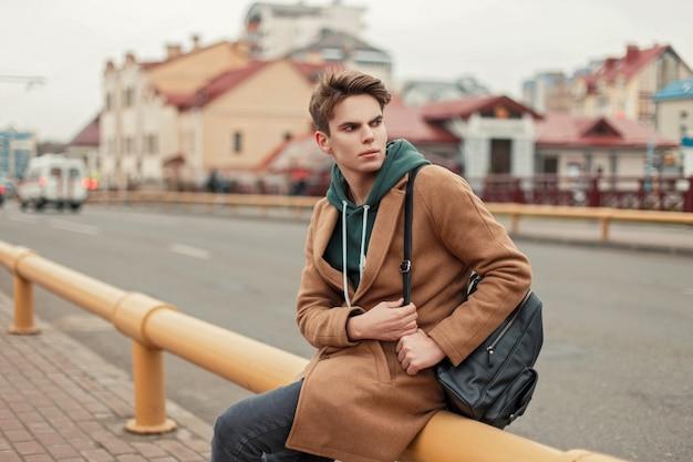 까마귀와 검은 가방이 도시의 거리에 앉아 유행 코트에 머리를 가진 세련된 젊은 남자