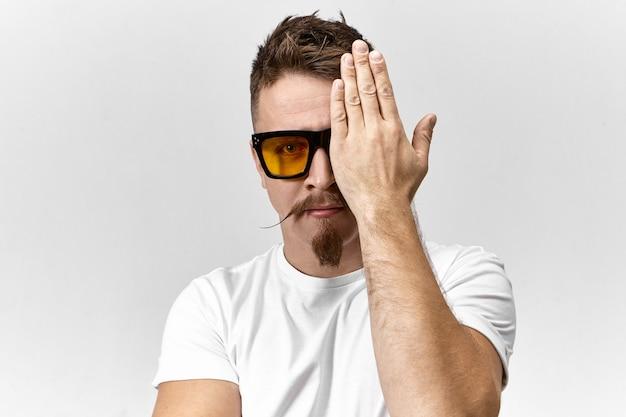 Giovane alla moda con occhiali da sole e maglietta bianca che nasconde un occhio