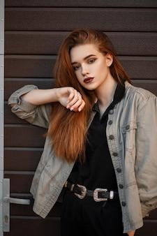 패션 재킷과 검은 폴로 거리에서 포즈를 취하는 세련된 젊은 모델 소녀