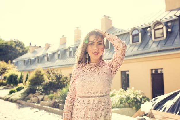 太陽の光の中で通りでポーズをとるファッショナブルなドレスのスタイリッシュな若いモデル。ヴィンテージ調色効果