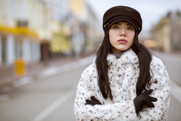 冬に屋外でポーズをとるキャップと毛皮のコートを着たスタイリッシュな若いモデル。空きスペース
