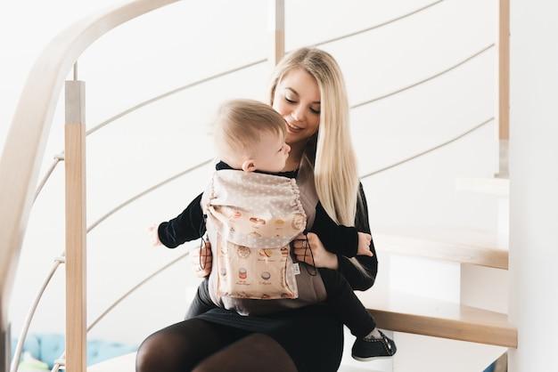Стильная молодая мама держит в эрго рюкзаке своего милого годовалого ребенка дома