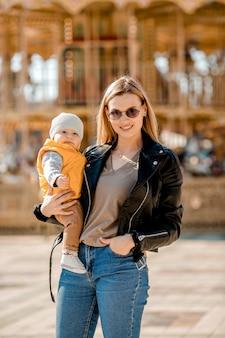 Стильная молодая мама гуляет с малышом в парке. счастливая мама