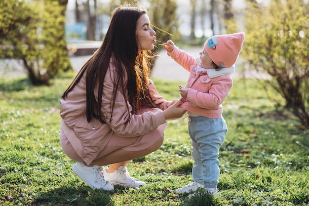 A stylish young mother and her little daughter have fun spending time together in the park