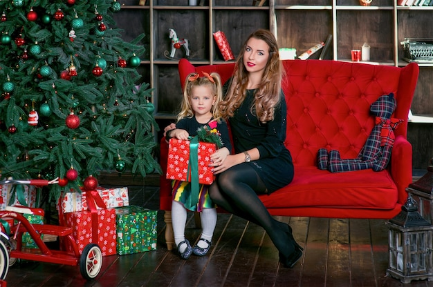 Stylish young mother with cute little daughter by the chrismas tree