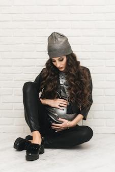 Стильная молодая беременная девушка в черной одежде с завитками на белой стене. фотографии в ожидании малыша