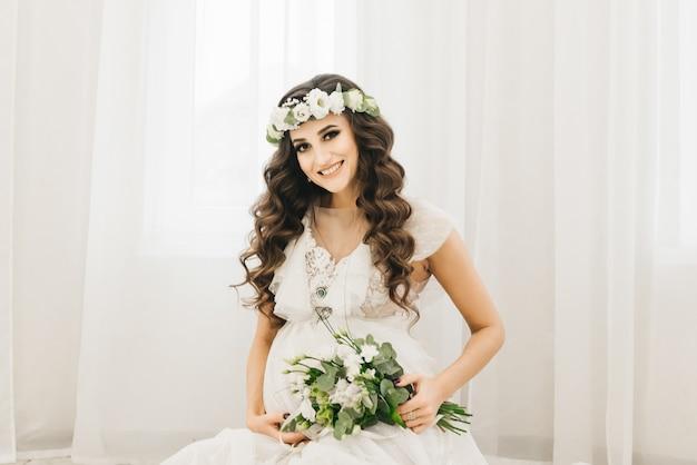 Стильная молодая беременная девушка в белой одежде с завитками и цветами. фотографии в ожидании малыша