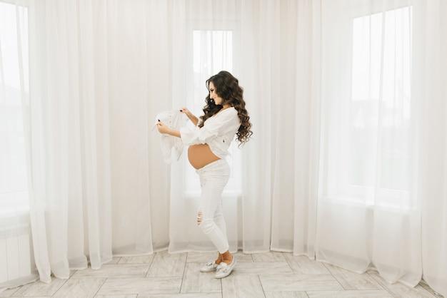 Стильная молодая беременная девушка в белой одежде с завитками, глядя детскую одежду. фотосессия в ожидании малыша