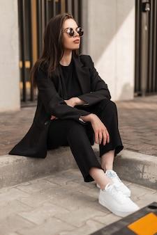 ブレザー、ズボン、白いスニーカーとファッショナブルな黒のアウターウェアのスタイリッシュな若いかわいい女の子が通りに座っています
