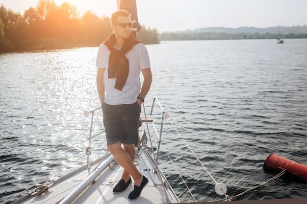 Стильный молодой матрос стоит на носу яхты. он позирует и смотрит в сторону