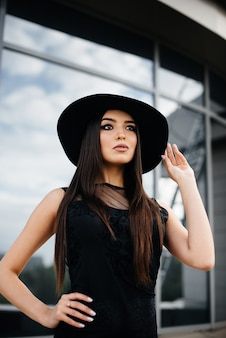 Stylish young and sexy girl posing in front of a business center in black