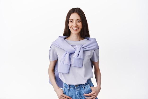 Elegante giovane donna snella in abito stile di vita, tenendosi per mano in tasca e sorridente davanti, in piedi casual in posa rilassata contro il muro bianco
