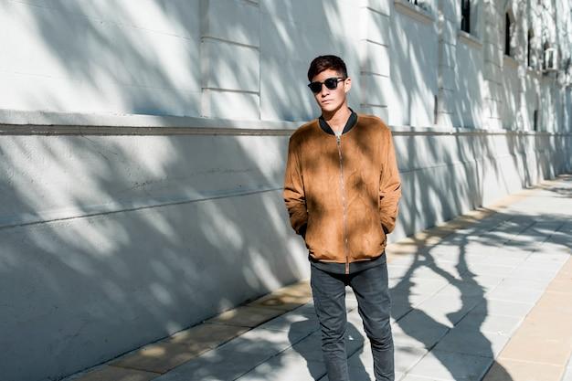 Stylish young teenage boy wearing brown jacket and black sunglasses walking on sidewalk