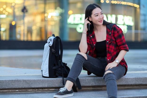 夜にバックパックと街のショッピングセンターの階段に座っているスタイリッシュな若い観光客の女性