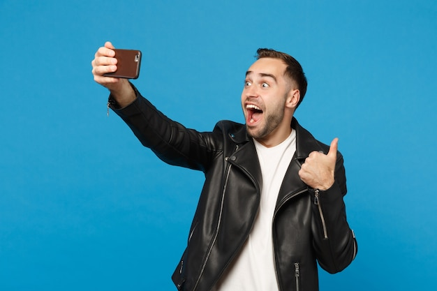 Stylish young unshaven man in black jacket white t-shirt oing selfie shot on mobile phone isolated on blue wall background studio portrait. people sincere emotions lifestyle concept mock up copy space