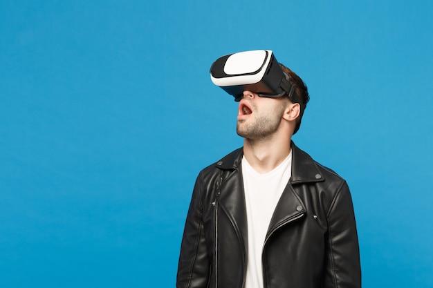 Стильный молодой небритый мужчина в черной куртке белой футболке, глядя в гарнитуру, виртуальная реальность vr, изолированных на синем стенном фоне студийного портрета. концепция образа жизни эмоции людей. копируйте пространство для копирования.