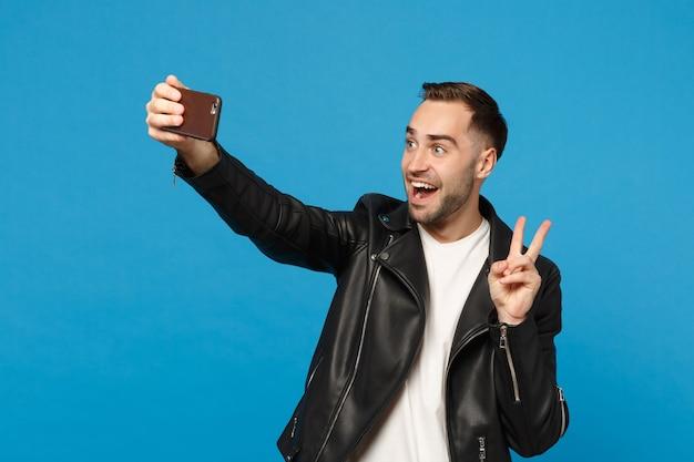 Стильный молодой небритый мужчина в черной куртке белой футболке oing selfie выстрелил на мобильный телефон, изолированные на синем фоне стены студийный портрет. люди искренние эмоции концепция образа жизни макет копией пространства