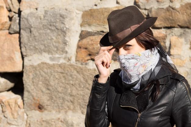 スタイリッシュな若い女性の盗賊が帽子をかぶって、コピースペースのある石の壁に向かって、顔の周りにスカーフを巻いて彼女の特徴を隠してカメラを見ています