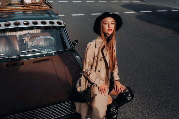 A stylish young woman in a beige coat and black hat on a city street sits on the hood of a car at sunset.