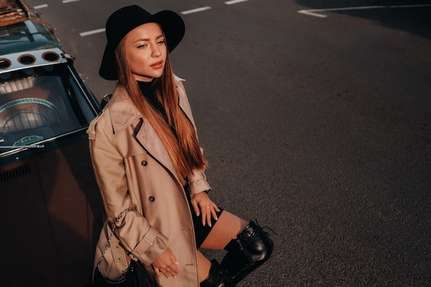 A stylish young woman in a beige coat and black hat on a city street sits on the hood of a car at sunset