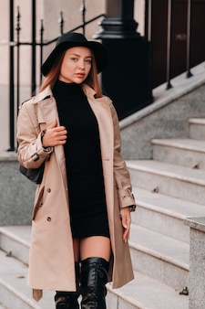 Stylish young woman in a beige coat in a black hat on a city street. women's street fashion. autumn clothing.urban style.