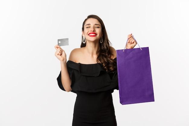 Elegante giovane donna in abito nero, andare a fare shopping, tenendo la borsa e una carta di credito, sorridendo compiaciuto, in piedi su sfondo bianco.