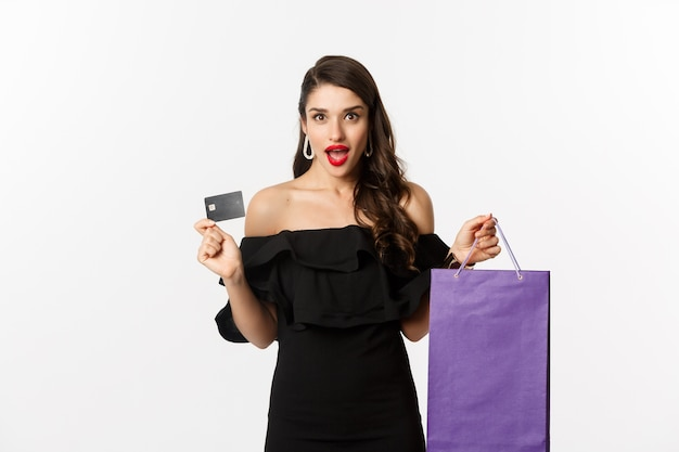 Stylish young woman in black dress going shopping, holding bag and credit card, smiling pleased, standing over white background.