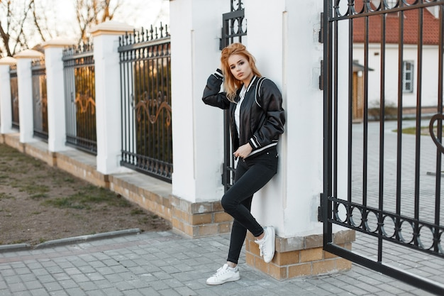 Stylish young woman in a black spring jacket in trendy jeans in a white polo shirt in sneakers posing near a vintage metal fence. american stylish girl. fashion