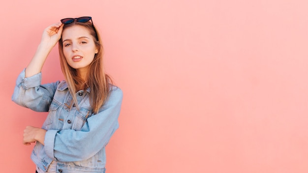 Stylish young woman in blue denim jacket standing against pink backdrop